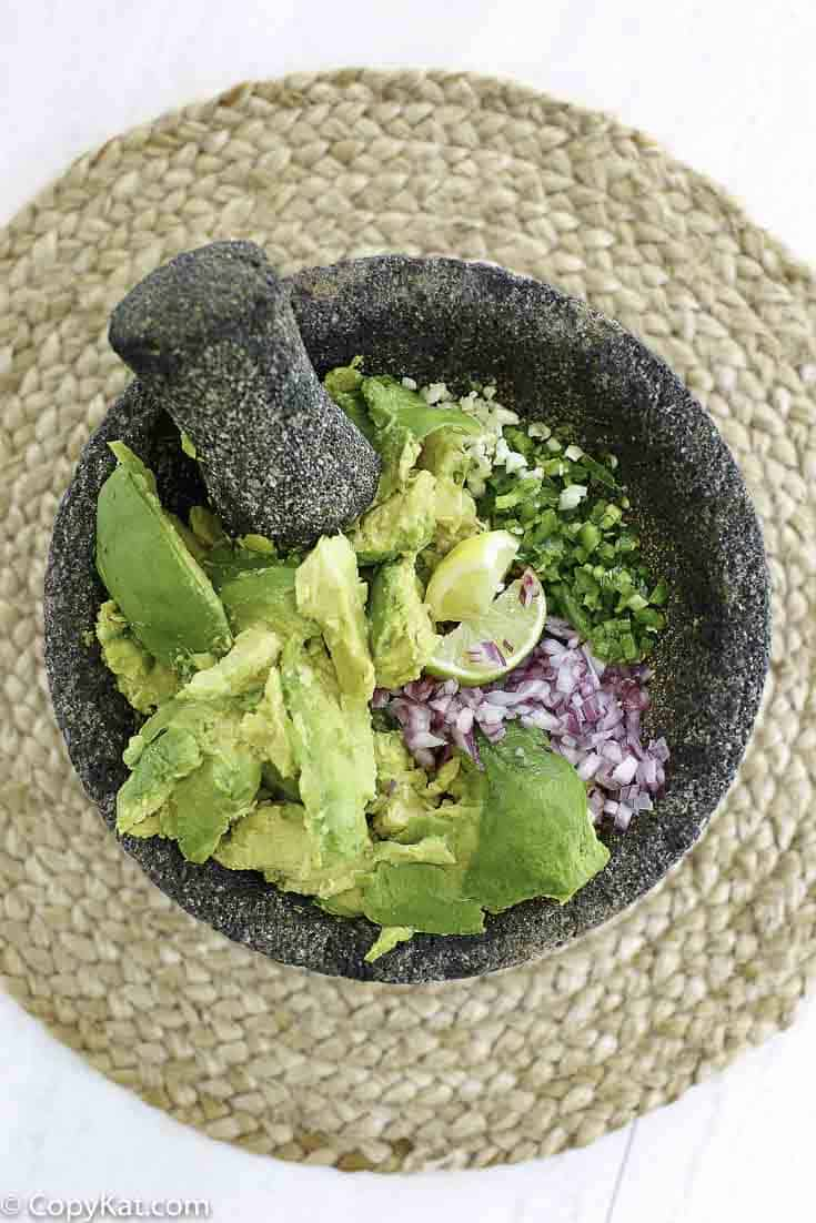 A motar and pestle with mashed avocados, red onions, jalapeno peppers, and more.