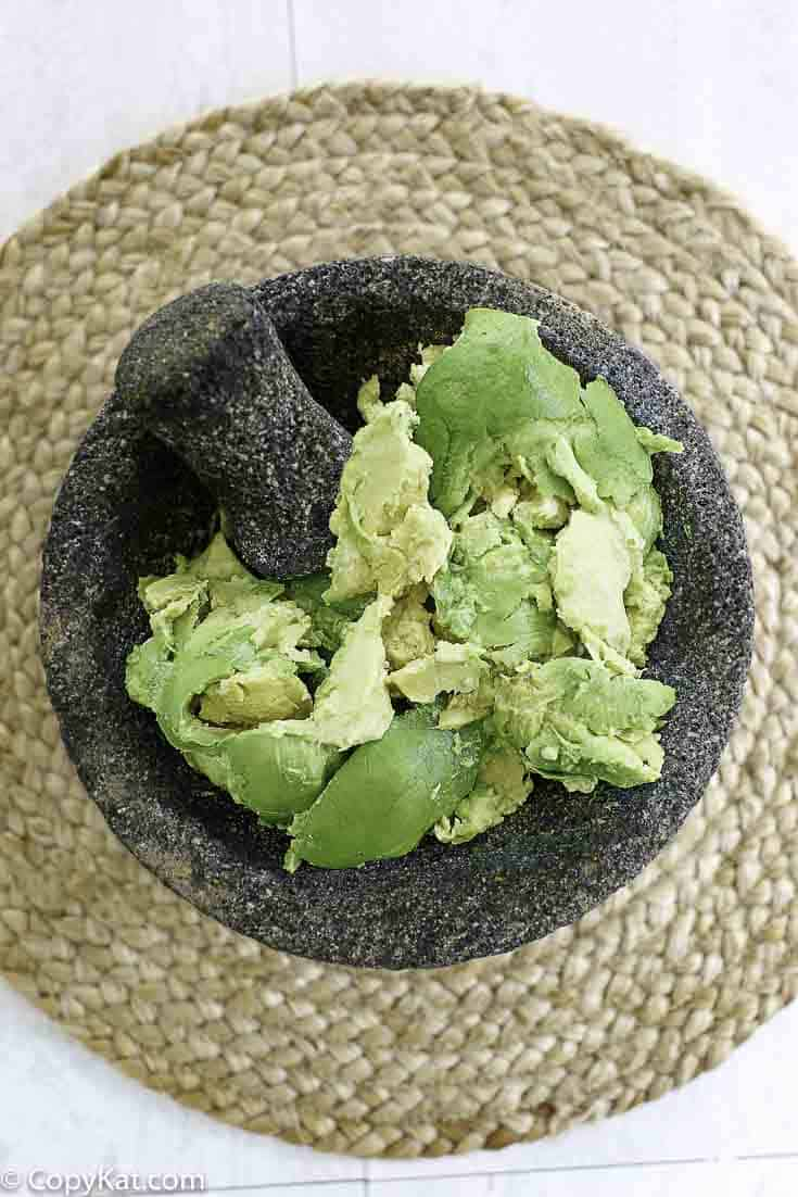 Mashing up avocados with a motor and pestle to make guacamole.