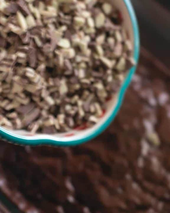 Pouring chopped Andes mints on top of a pan of hot brownies.
