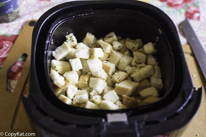 Uncooked croutons in an air fryer basket