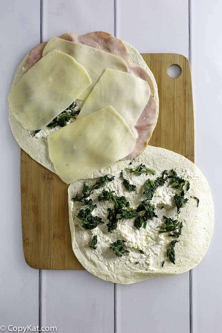 layering ham, cheese, and spinach on tortilla to make pinwheels