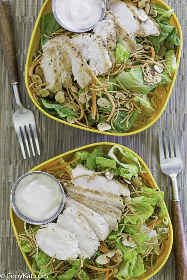 Two bowls of salad with grilled chicken and oriental dressing