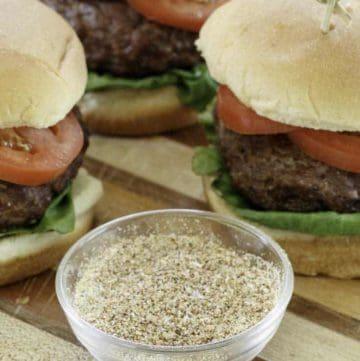 homemade burger seasoning and hamburgers on a wood cutting board.