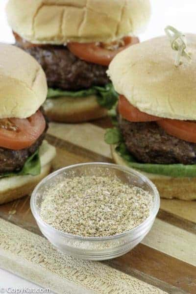 homemade burger seasoning and hamburgers on a wood cutting board.