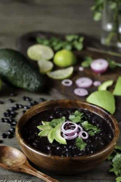 a bowl of cooked black beans with cilantro, lime, red onion and avocado.