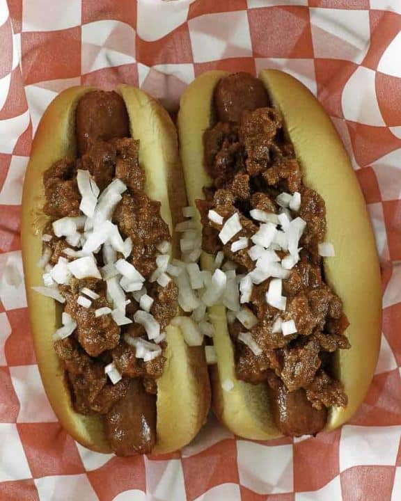 chili con carne on top of hot dogs