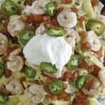 Cheesy nachos with shrimp, cheese, sour cream and more
