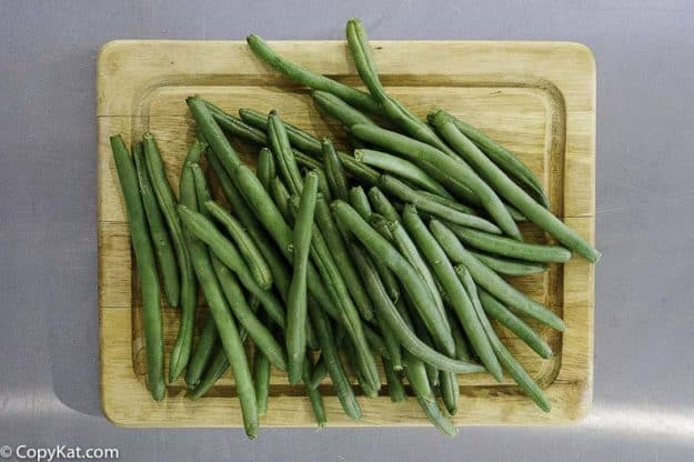 fresh green beans on a wood cutting board