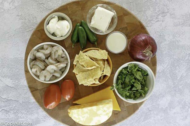 shrimp, cheese, cilantro, sour cream, corn chips on a board to make shrimp nachos