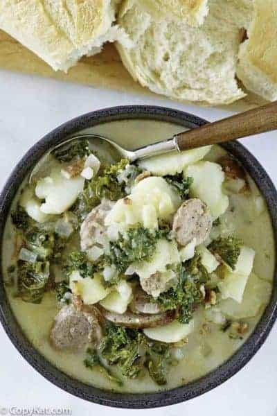 a bowl of potato and sausage soup with kale