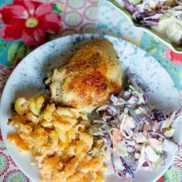 Baked chicken, cole slaw, and macaroni and cheese on a plate