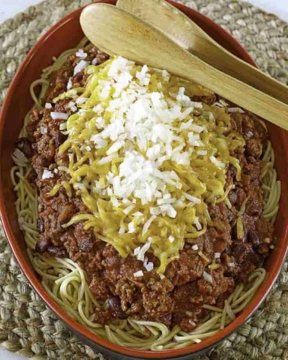 a plate of five way chili with spaghetti, chili, cheese, onions, and more