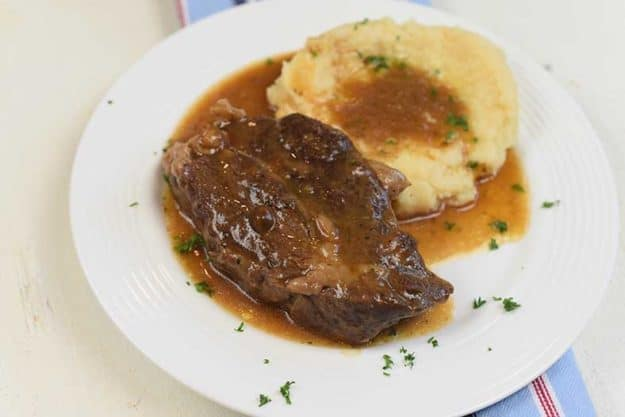 pot roast with mashed potatoes and gravy on a plate