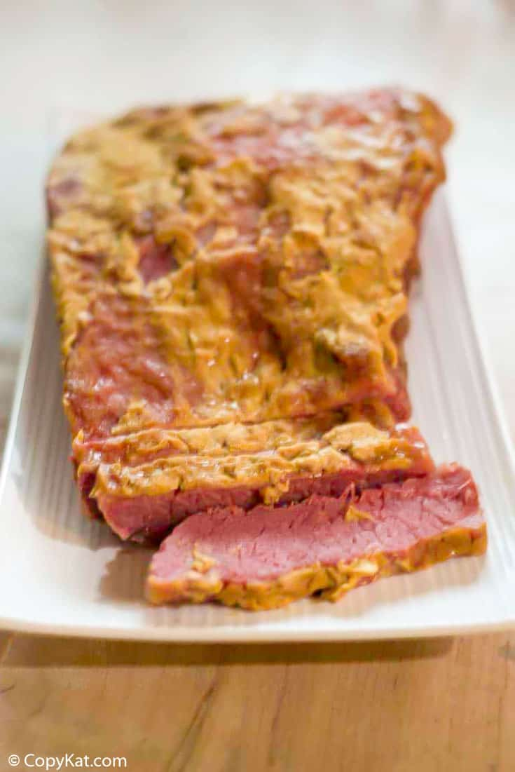 baked corned beef brisket with brown sugar and dijon mustard on a platter