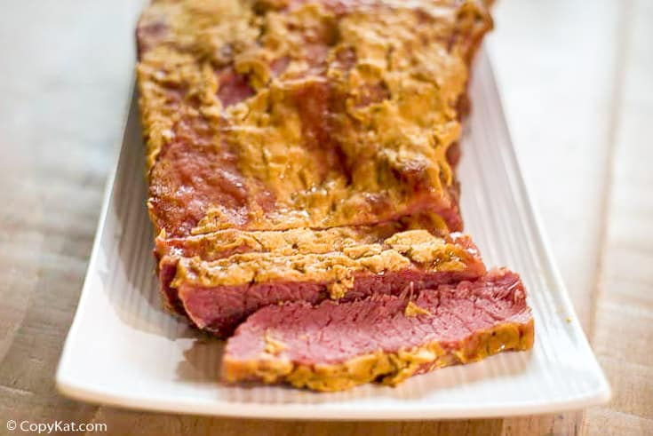 Baked corned beef brisket with mustard and brown sugar on a platter