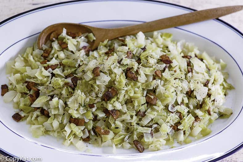 a serving dish with boiled cabbage with bacon