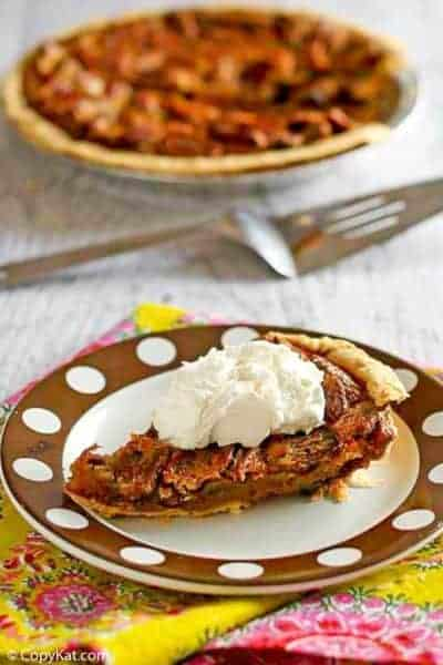 a slice of chocolate pecan pie topped with whipped cream