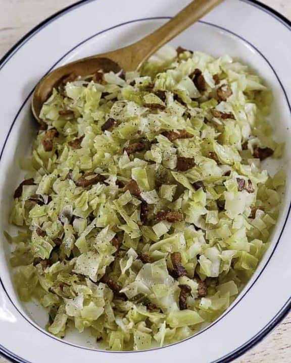 a plate of boiled cabbage with bacon