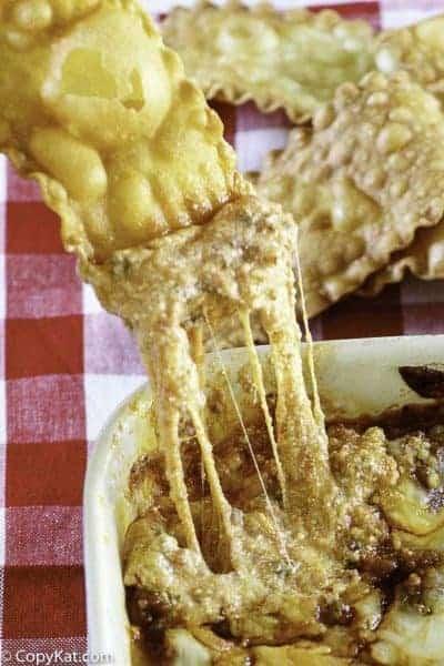 a pasta chip dipping into cheesy lasagna dip
