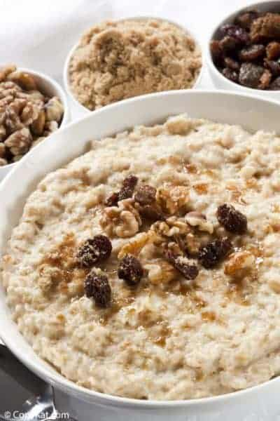 a bowl of oatmeal topped with raisins, walnuts, and brown sugar