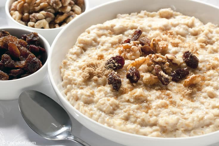 a bowl of oatmeal with raisins, walnuts, and brown sugar