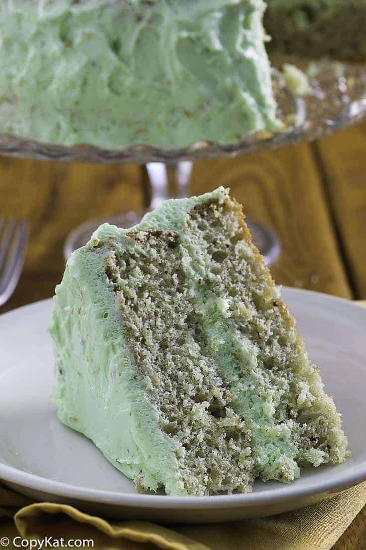 A slice of pistachio cake on a plate with the cake in the background.