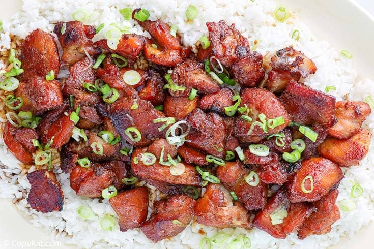 a platter of bourbon chicken on top of white rice