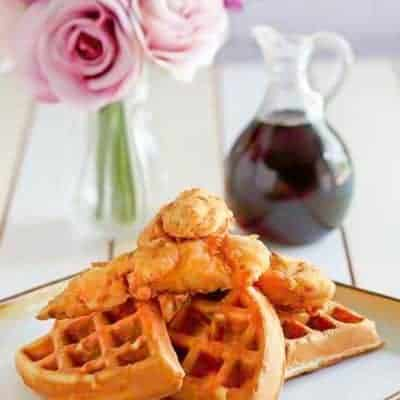 Homemade Grand Lux Cafe Chicken and Waffles served with a bottle of syrup