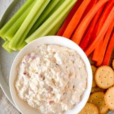 old fashioned pimento cheese spread on a platter with celery, carrots, and crackers