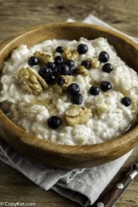 A bowl of oat bran porridge with walnuts and blueberries