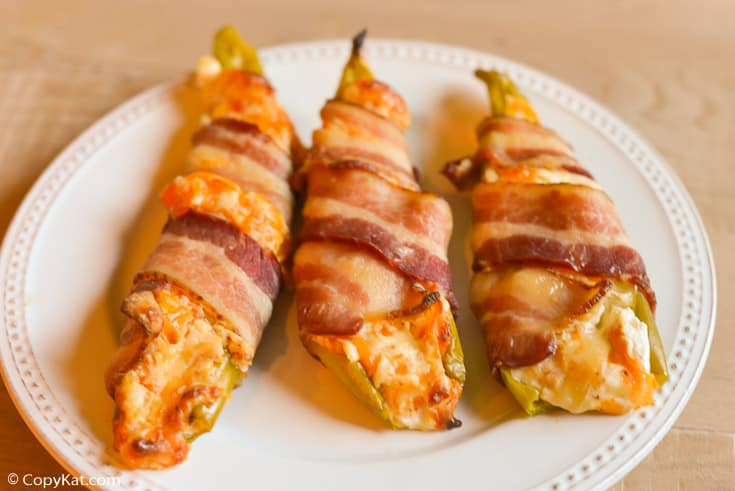 three bacon wrapped stuffed hatch peppers on a plate