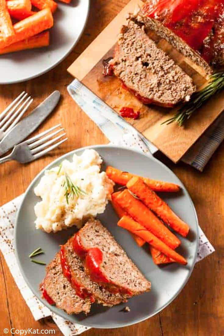Homemade meatloaf with ketchup sauce served with mashed potatoes and carrots