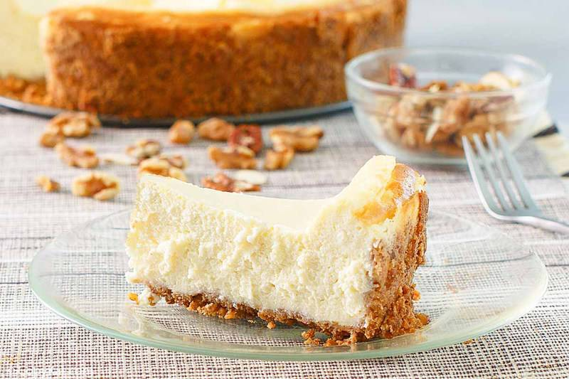 a slice of cheesecake in front of nuts and a cheesecake