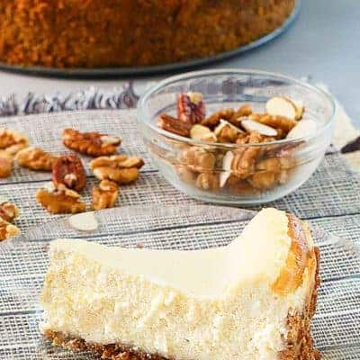 a slice of cheesecake, nuts, and a cheesecake on platter