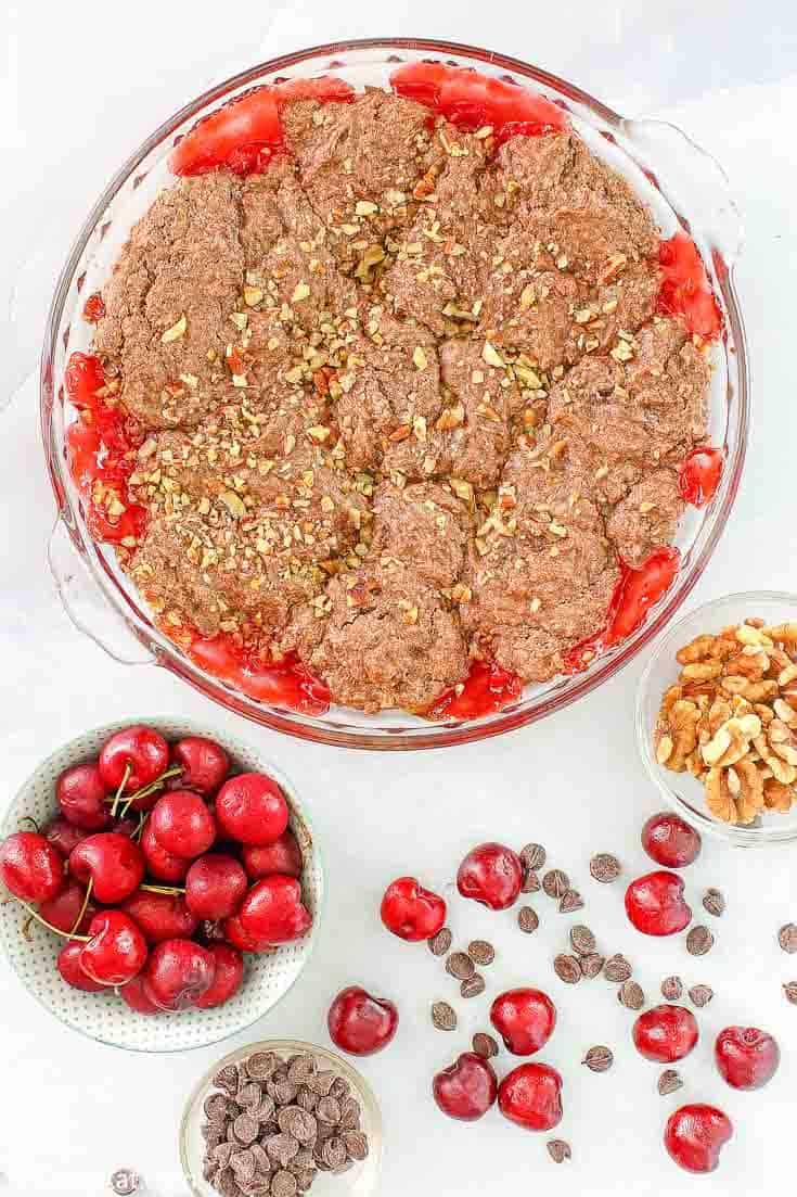 zapatero de cereza y chocolate con cerezas, chispas de chocolate y nueces al lado