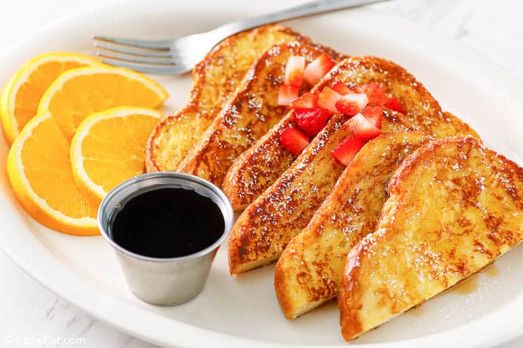 French toast with syrup, chopped strawberries, and orange slices