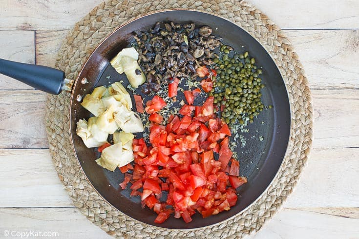 artichoke hearts, olives, tomatoes, and capers in a skillet