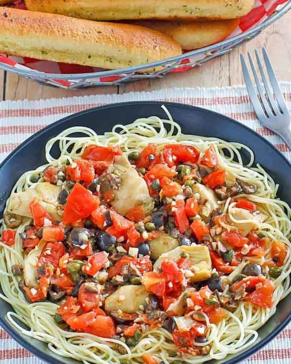 angel hair pasta with artichokes and a basket of breadsticks