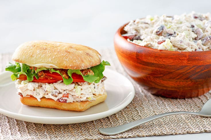 homemade Newks chicken salad in a sandwich and a wood bowl