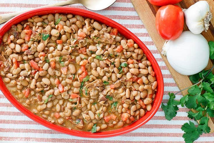 Frijoles a la Charra (Charro Beans) in a red serving dish