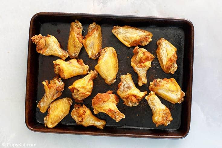 crispy fried chicken wings on a baking sheet