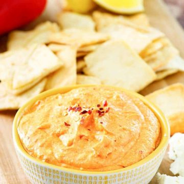 a bowl of roasted red pepper dip next to crackers
