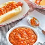 homemade Sabrett onion sauce in a bowl and on two hot dogs