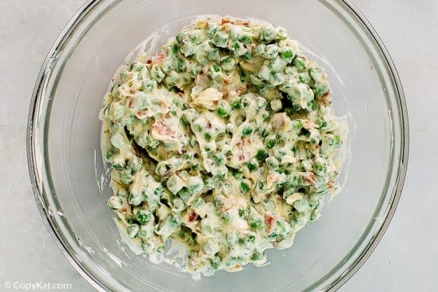 peas, carrots, bacon, and ranch dressing together in a glass bowl