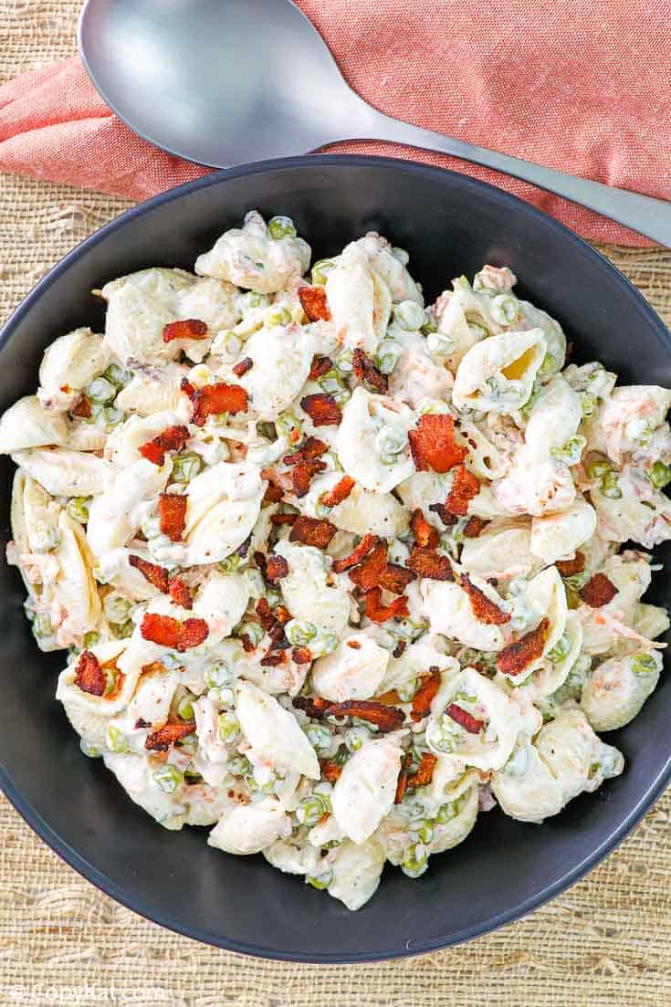 pasta salad with bacon, peas, carrots, and ranch dressing in a black bowl