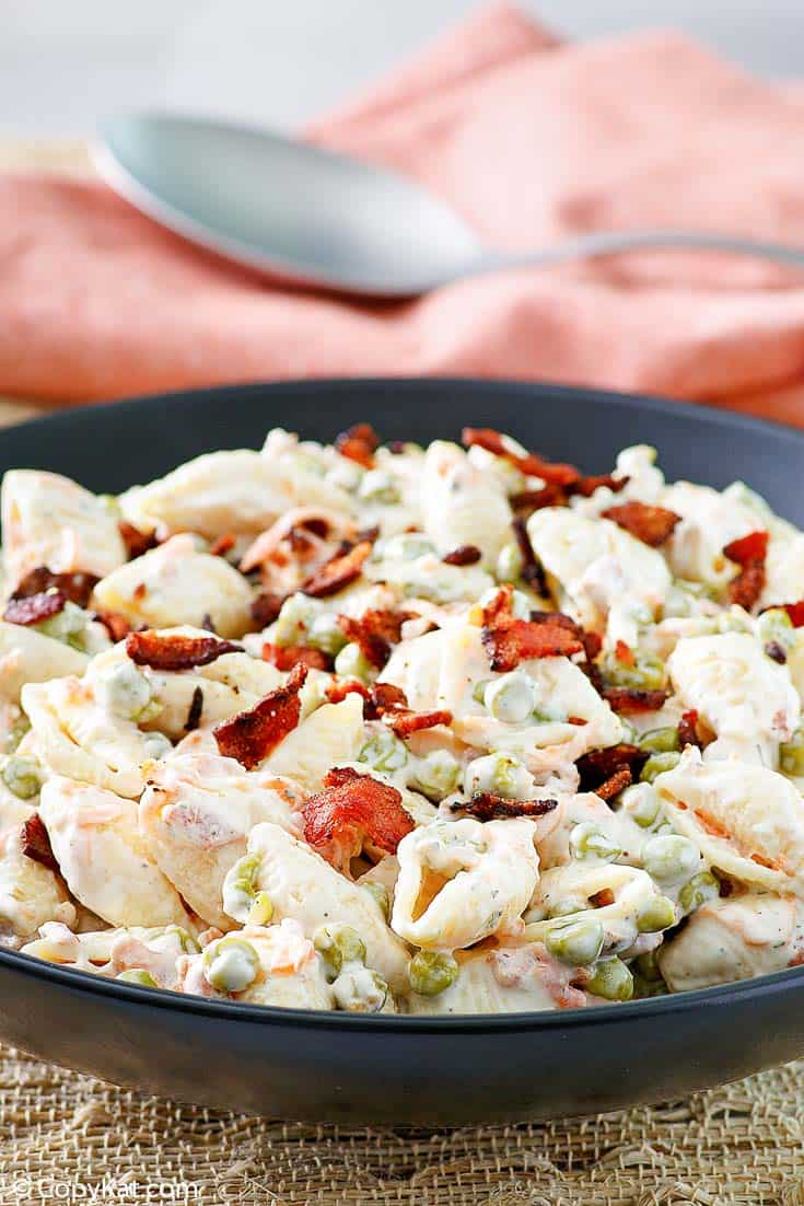 a bowl of pasta salad with bacon, carrots, peas, and ranch dressing