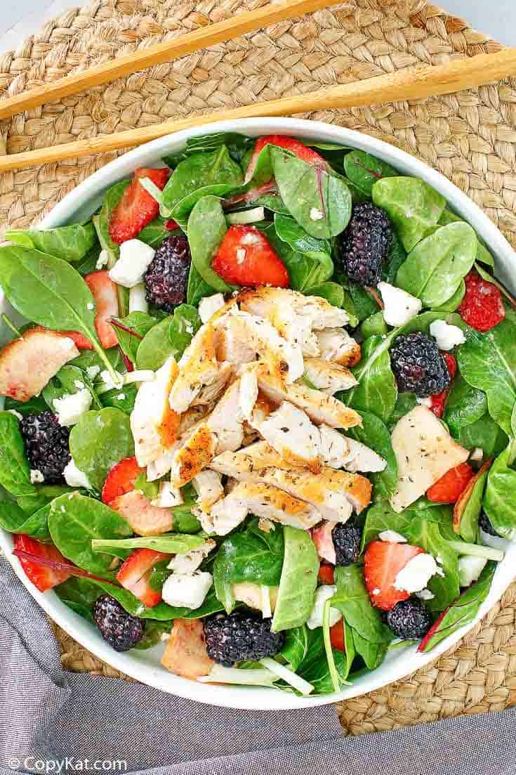 a bowl of salad with chicken, berries, and feta cheese