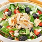 a salad with grilled chicken, berries, apples, and feta cheese