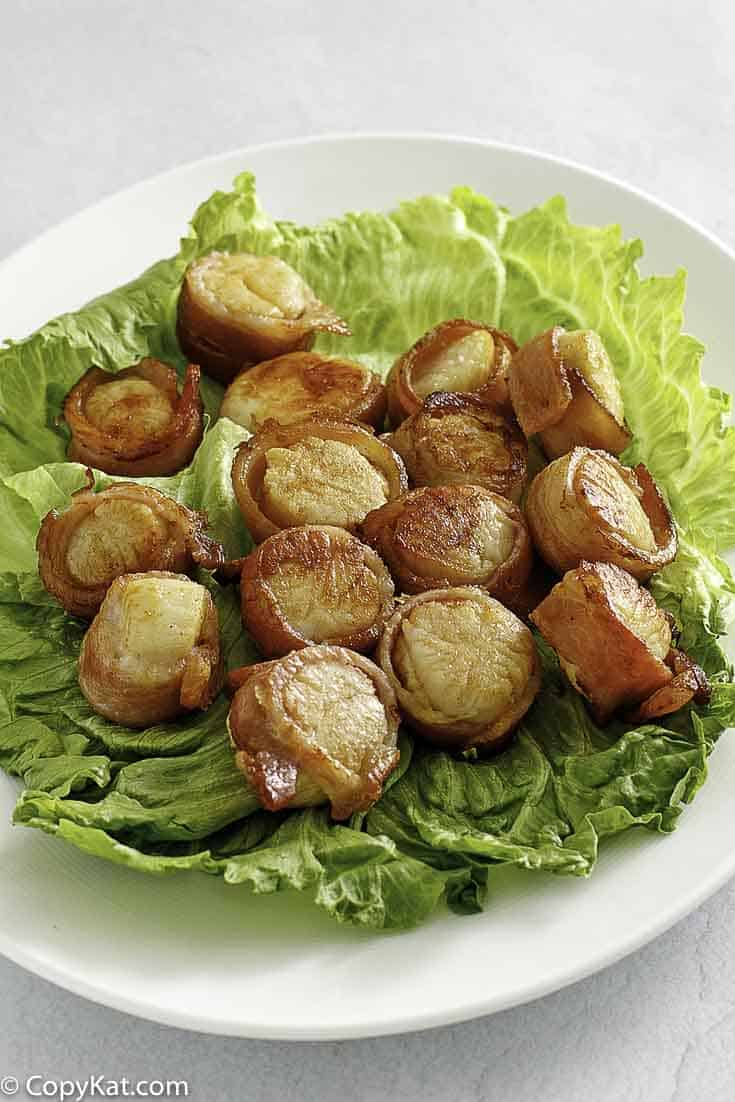 bacon wrapped scallops on top of lettuce on a platter