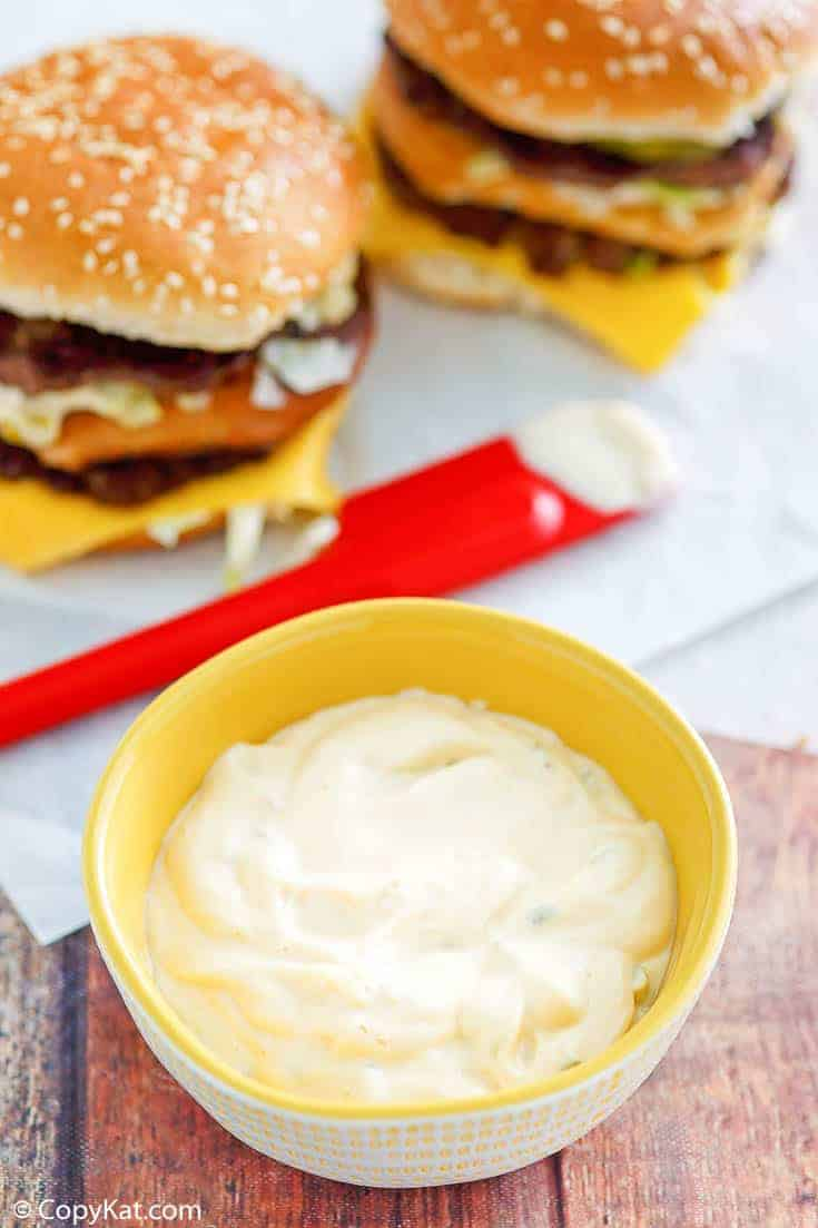 homemade Big Mac special sauce in a small bowl and two homemade Big Mac burgers